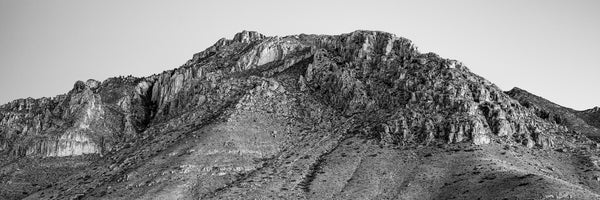 Black and white panoramic landscape photograph of the massive, rugged, and rocky peaks of the Guadalupe Mountains.