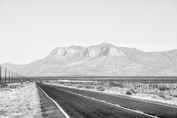 Black and white landscape photograph of a lonesome highway through the vast silent desert.