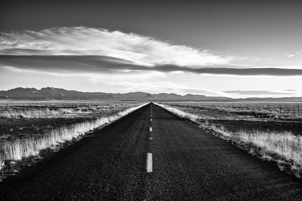 Black and white landscape photograph of a highway to the distant mountains seen in the first morning light.