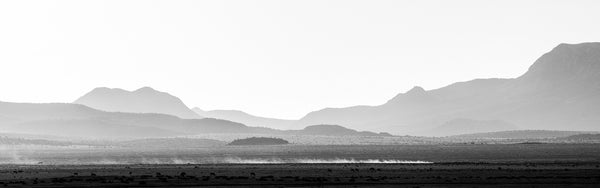 Black and white panoramic landscape photograph that shows a pickup truck crossing the desert at sunrise, leaving a cloud of dust in its wake, with layers of rugged western mountains in the background.