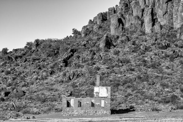 Black and white photograph of a big abandoned brick ruin at the base of a mountain in the western desert.