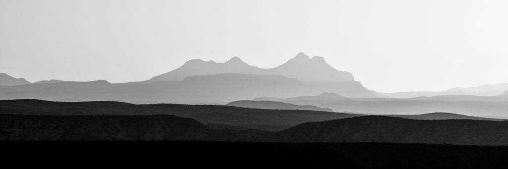 Black and white panoramic landscape photograph of layers upon layers of rugged western mountains at sunrise.