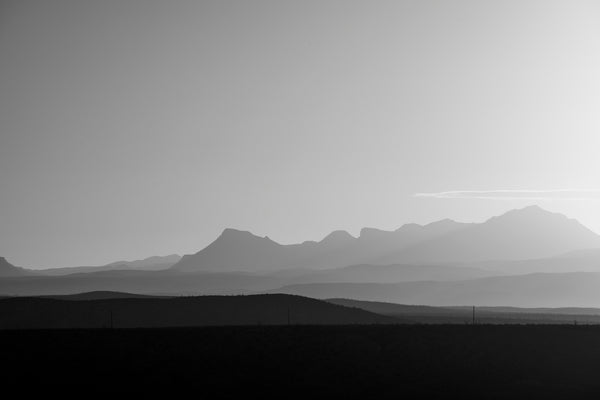 Black and white landscape photograph of hazy mountain layers at sunrise.