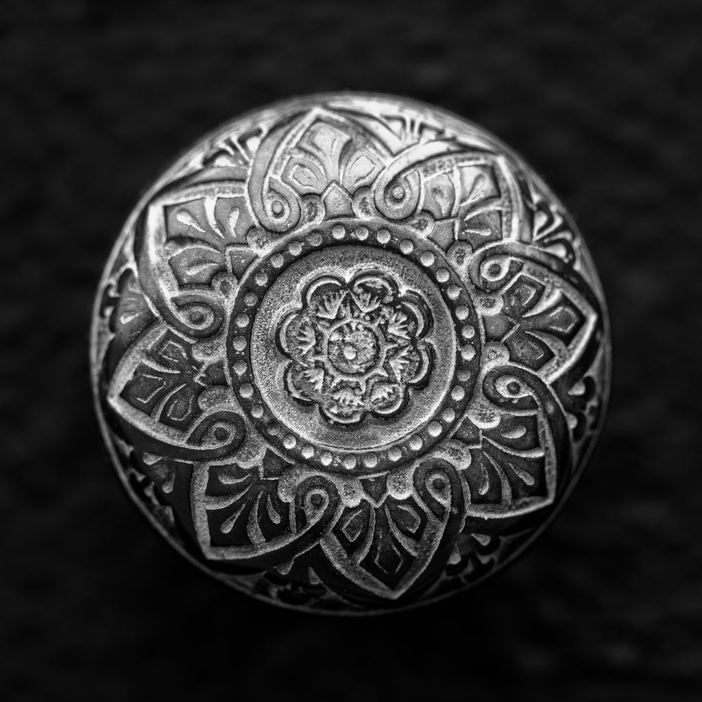 Black and white photograph of the designs on an ornate antique brass door knob found on a historic library building in the American Midwest. (Square format)