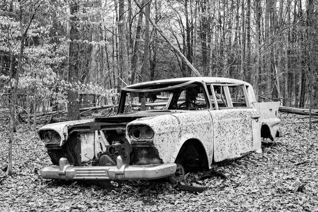 Black and white photograph of an abandoned classic automobile left sitting in the forest.