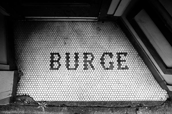 "Black and white photograph of the custom tile entry to a business that was once owned by someone named ""Burge"" in a building constructed in 1915."