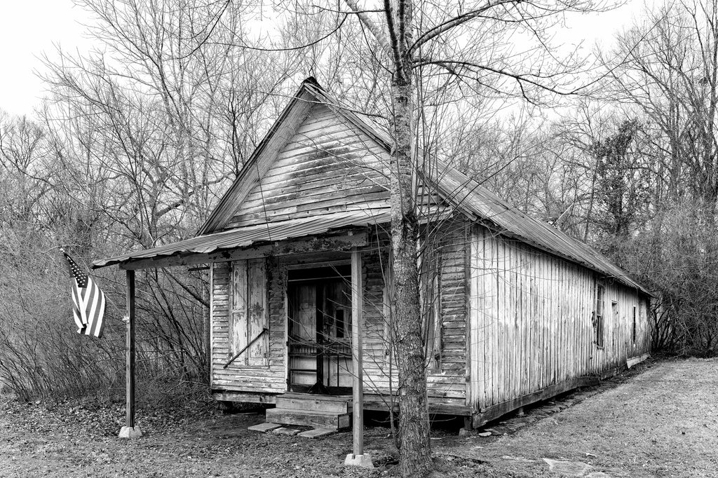 Black and white photograph of an old, abandoned country store with a rusty tin roof, peeling paint, and tattered screen doors, discovered along a back road.