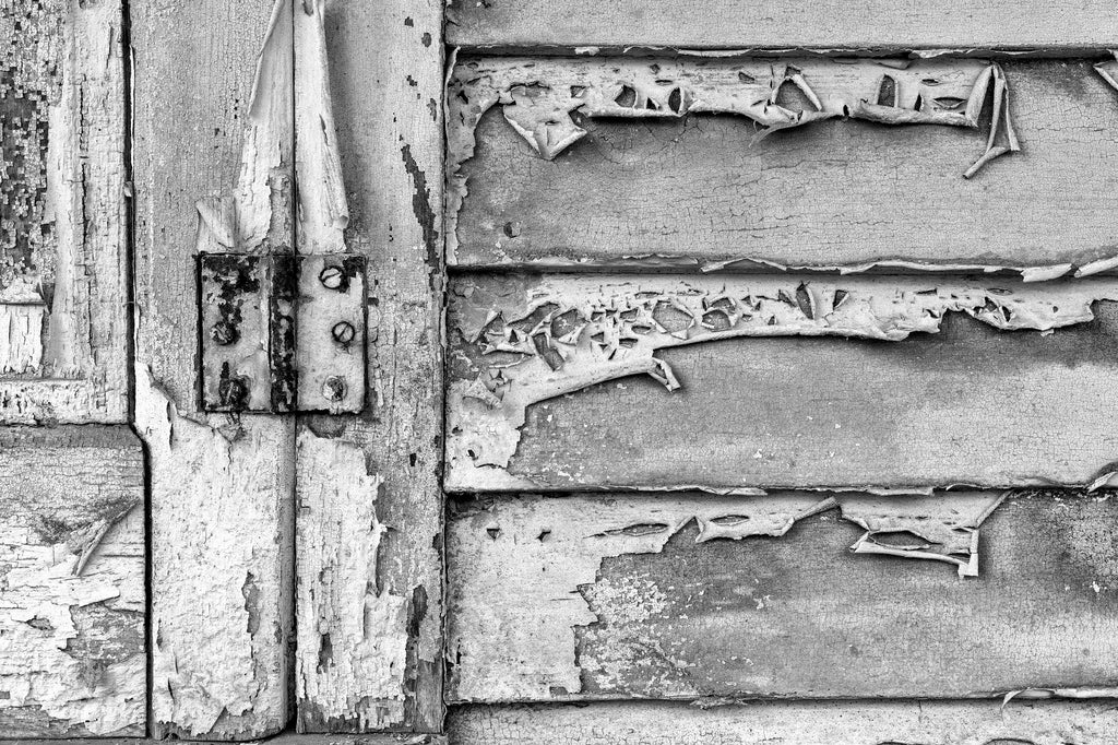Black and white photograph of peeling paint on the weathered boards of an abandoned historic mercantile store found along a back road in the deep south.