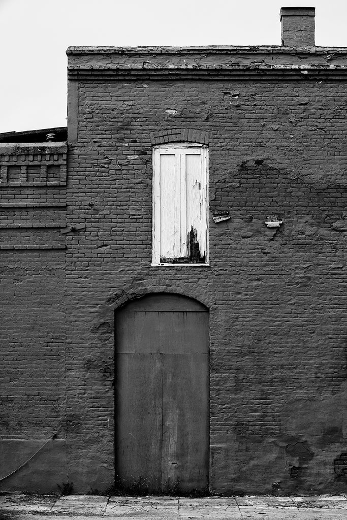 Black and white photograph of an old brick building in a small town painted all across with dark red paint, except for the white wooden shutters on a single window