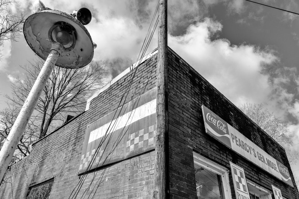 Black and white photograph of vintage signs on the exterior of an abandoned old country store.