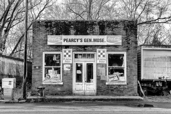 Black and white photograph of an abandoned country store with vintage ads on its exterior.