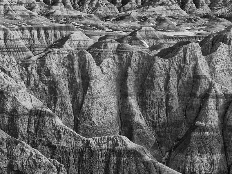 Black and white landscape photograph of the rugged, wrinkled and treeless terrain at the Badlands of South Dakota.