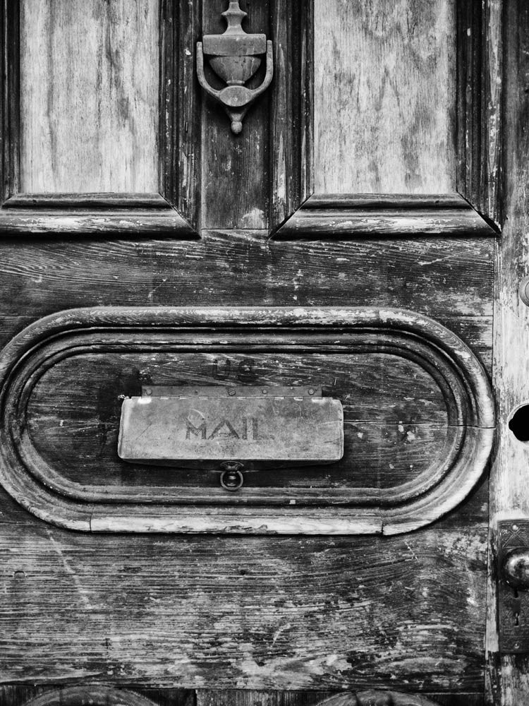 Black and white photograph of a textured, old, wooden door with a mail slot, seen in the French Quarter of New Orleans, Louisiana.