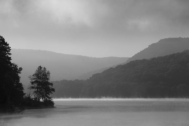 Black and white photograph of a lake surrounded by hills in early morning, as mists rise from the surface of the water, creating a mysterious mood.