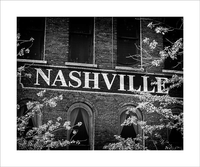 "Black and white photograph of ""Nashville"" painted on the bricks of an old building in downtown Nashville.  This photograph can be seen in the Nashville Room, a private dining room at Nashville's amazing Prima Restaurant in the Gulch neighborhood. At 16"" x 20,"" this is the exact size and finish as the print at Prima -- just add your own top mat and framing.  This photograph is also available in other sizes. Go to the main Nashville gallery."