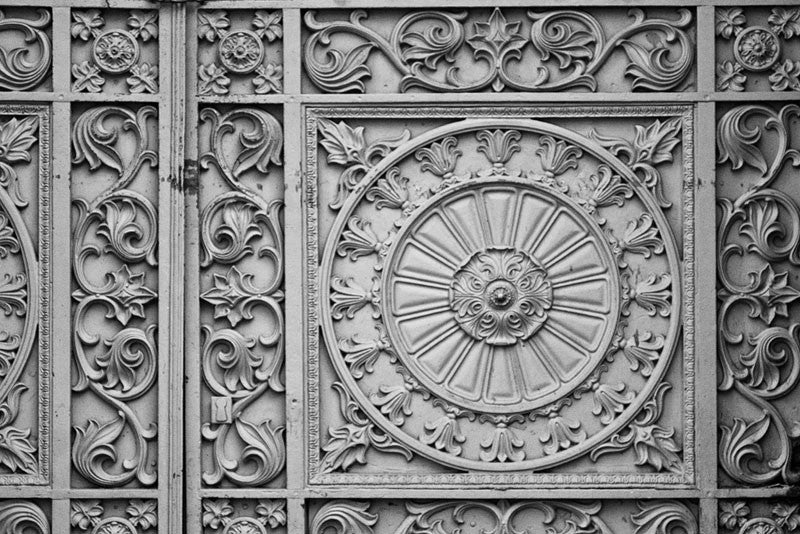 Black and white architectural detail photograph of beautiful, decorative metalwork flourishes in the French Quarter of New Orleans.