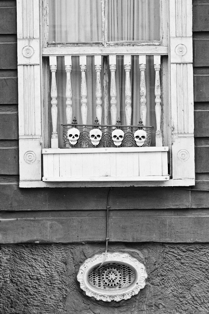 Black and white architectural detail photograph of a house in the New Orleans French Quarter, with little skulls on the window.