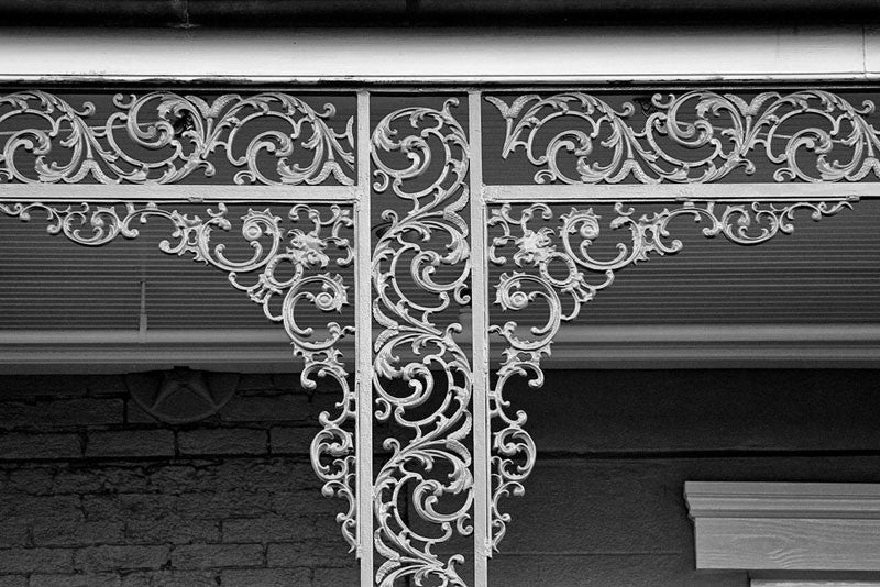 Black and white architectural detail photograph of iconic, decorative balcony ironwork flourishes in the French Quarter of New Orleans. New Orleans is famous for its romantic balconies with their fanciful ironwork railings.