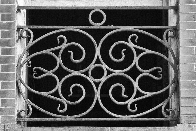 Black and white architectural detail photograph of a New Orleans window with a decorative ironwork screen.