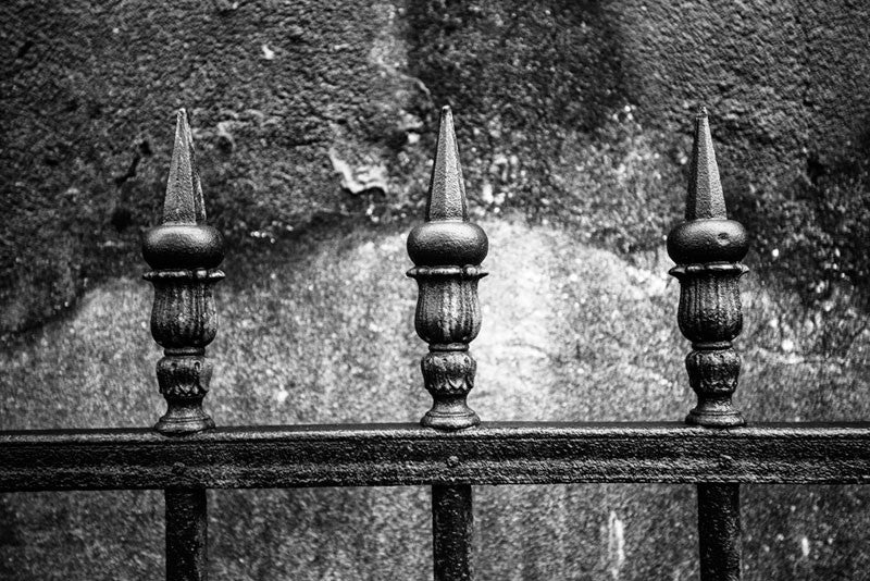 Black and white fine art photograph of three pointed pickets of an iron fence near a textural cement wall photographed on a rainy morning in New Orleans, Louisiana.