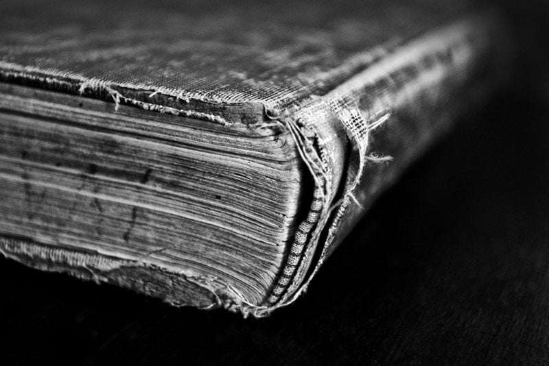 Black and white photograph of a tattered and worn old book a short history of