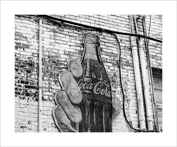 "Black and white photograph of a grimy alley in downtown Nashville, with paint peeling from the brick walls, and a large vintage advertisement for Coca Cola.  This photograph can be seen in the Nashville Room, a private dining room at Nashville's amazing Prima Restaurant in the Gulch neighborhood. At 16"" x 20,"" this is the exact size and finish as the print at Prima -- just add your own top mat and framing."