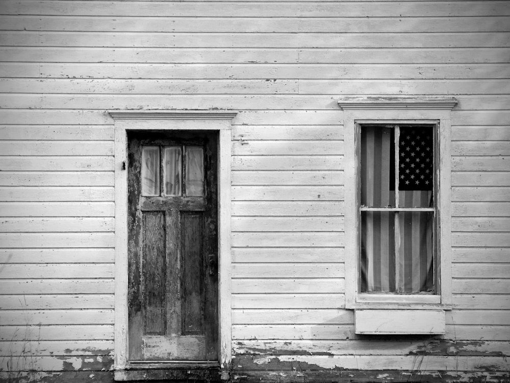 Black and white photograph of a little white house with a US flag hanging in the front window.