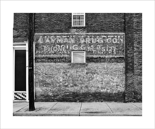 "Black and white photograph of layers of peeling painted ads on the side of an old pharmacy building in South Nashville.  This photograph can be seen in the Nashville Room, a private dining room at Nashville's amazing Prima Restaurant in the Gulch neighborhood. At 16"" x 20,"" this is the exact size and finish as the print at Prima -- just add your own top mat and framing."