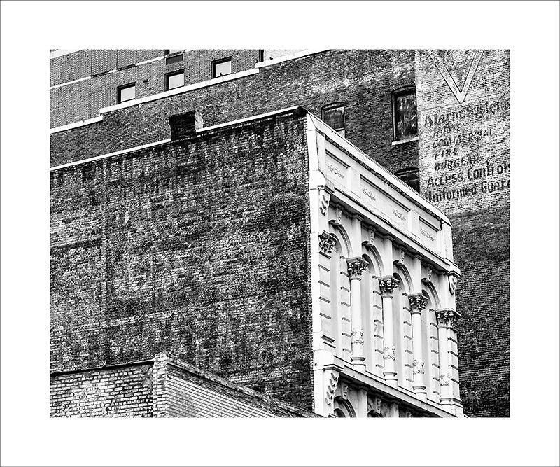"Black and white photograph historic buildings in downtown Nashville, featuring fading and peeling painted ads on their expansive brick walls.  This photograph can be seen in the Nashville Room, a private dining room at Nashville's amazing Prima Restaurant in the Gulch neighborhood. At 16"" x 20,"" this is the exact size and finish as the print at Prima -- just add your own top mat and framing."
