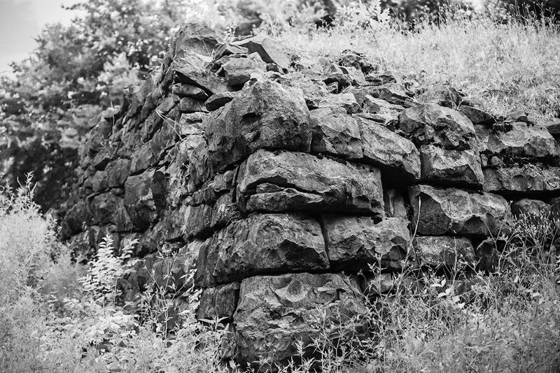 Black and white photograph of the old limestone walls of Fort Negley on a hillside near Nashville. Fort Negley is a star-shaped structure built of limestone blocks on a hilltop south of the city, and was the largest inland fort built during the American Civil War. The fort was built by the Union army in 1862 as a defensive post after the Confederates lost control of Nashville in successive battles, but with fighting concentrated in other areas, the fort never saw action.