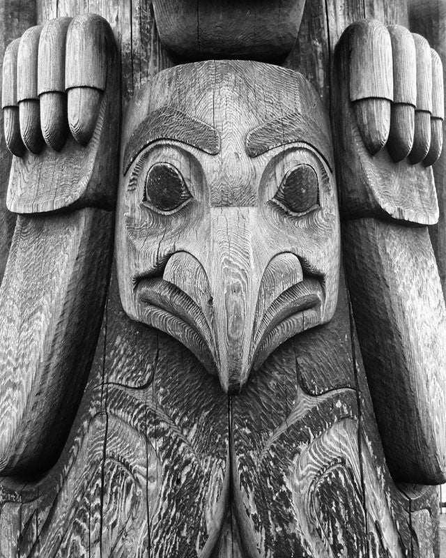 Black and white detail photograph of the bird figure on the totem pole that stands on the Seattle waterfront.