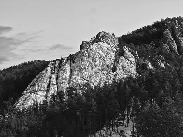 Black and white landscape photograph of the beautiful Black Hills of South Dakota, featuring a large rock outcropping among the dark pine trees.