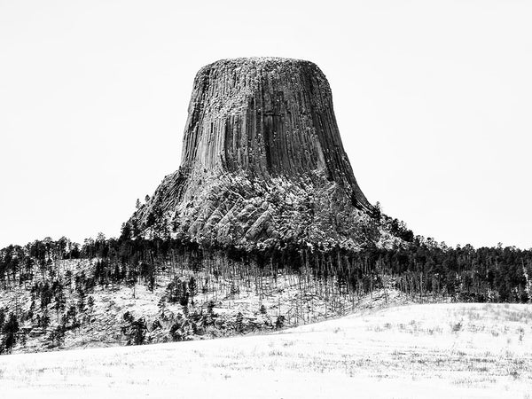 Black and white landscape photograph of Devil's Tower, Wyoming in winter.