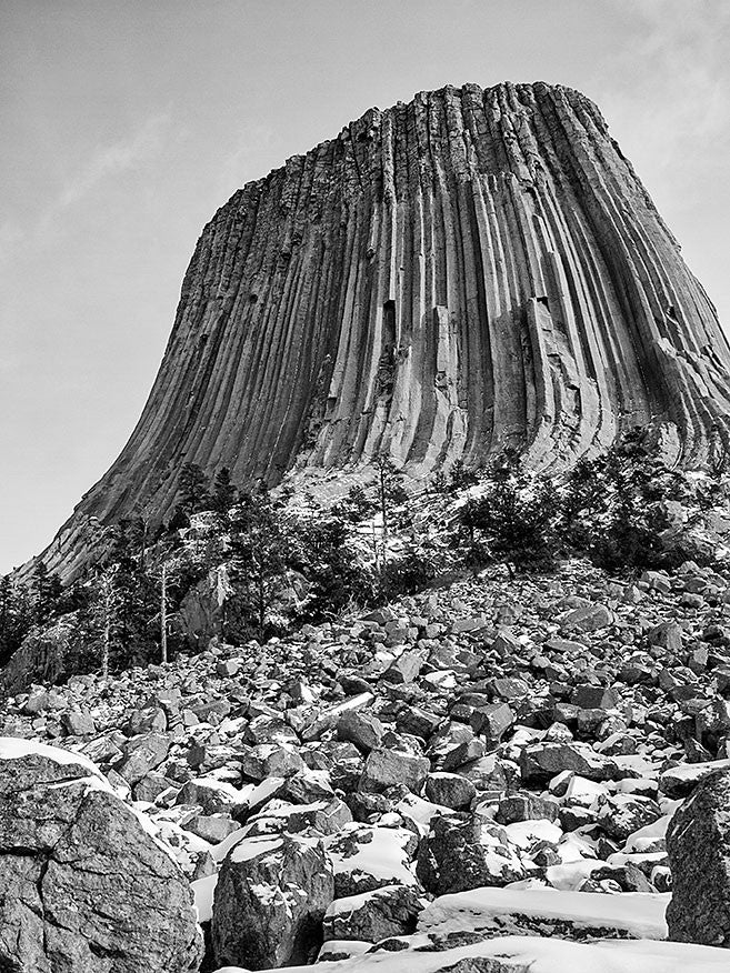 Black and white landscape photograph of Devil's Tower, Wyoming, seen from below where stone rubble has collected near the base.