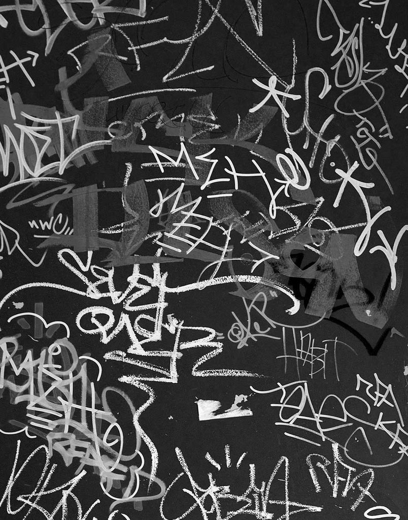 Black and white photograph of layers of graffiti tags on a door in downtown Madison, Wisconsin. The elaborate markings give the impression of an abstract painting.