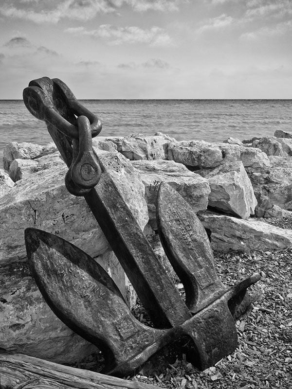 Black and white photograph of a ship's anchor perched against rocks on the shore of Lake Michigan in Wisconsin.
