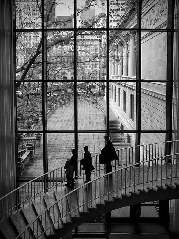 Black and white photograph inside the Art Institute of Chicago, with large windows looking out to Michigan Avenue in downtown Chicago.