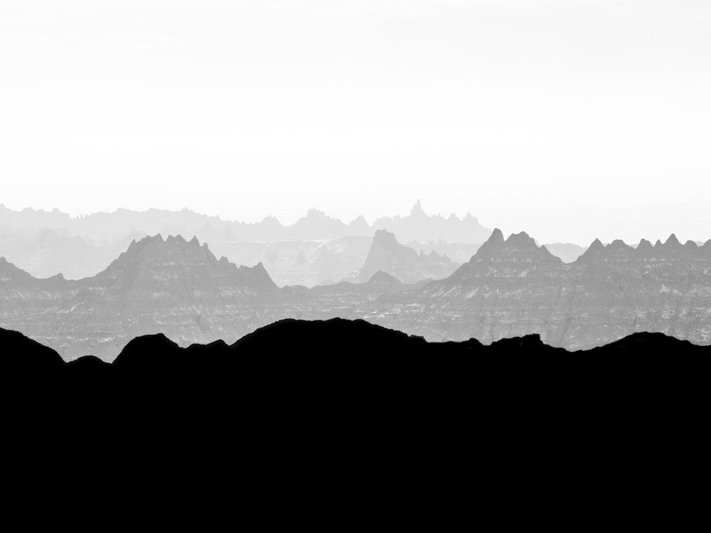 Black and white landscape photograph of misty peaks in early morning light at the Badlands of South Dakota.