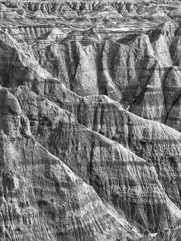 Black and white landscape photograph of the rugged, wrinkled, and treeless terrain at the Badlands of South Dakota.