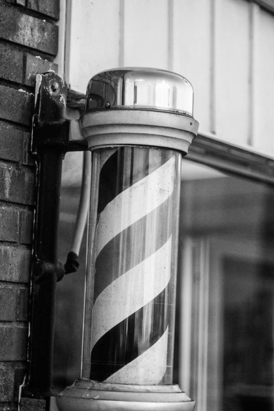 Black and white photograph of a barber pole outside an old-fashioned southern barber shop in downtown Murfreesboro, Tennessee.