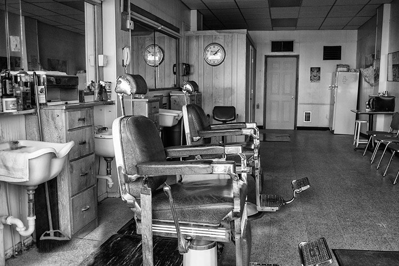 Black and white photograph inside a small town barber shop.