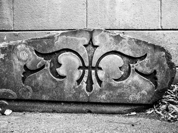 Black and white landscape photograph of a broken architectural fragment with a carved design sitting in a parking lot
