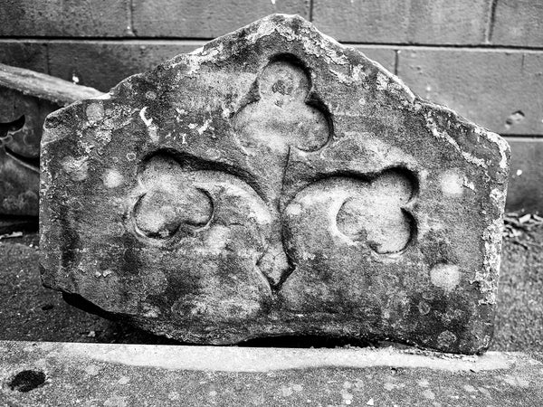 Black and White Photograph of a broken Carved Stone Architectural Fragment with Shamrock Design