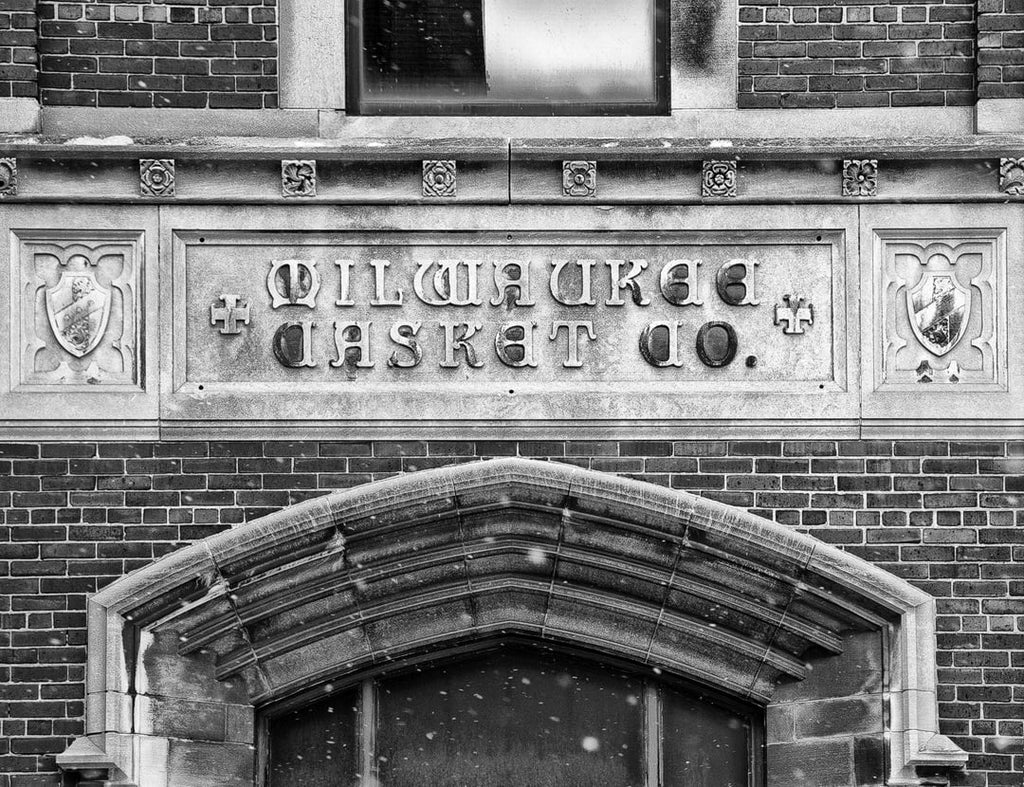 Black and white photograph of the sign on the old Milwaukee Casket Co. building in downtown Milwaukee. This Neogothic Revival building was constructed in 1929 at 1418 West St. Paul Avenue in Milwaukee. The location served as a shipping operation for Milwaukee Casket Company, and was later an air conditioning/heating repair service.