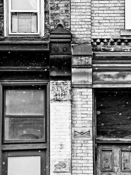 Black and white architectural detail photograph of the seam where two old buildings in old Milwaukee meet, with snow flying in the air.