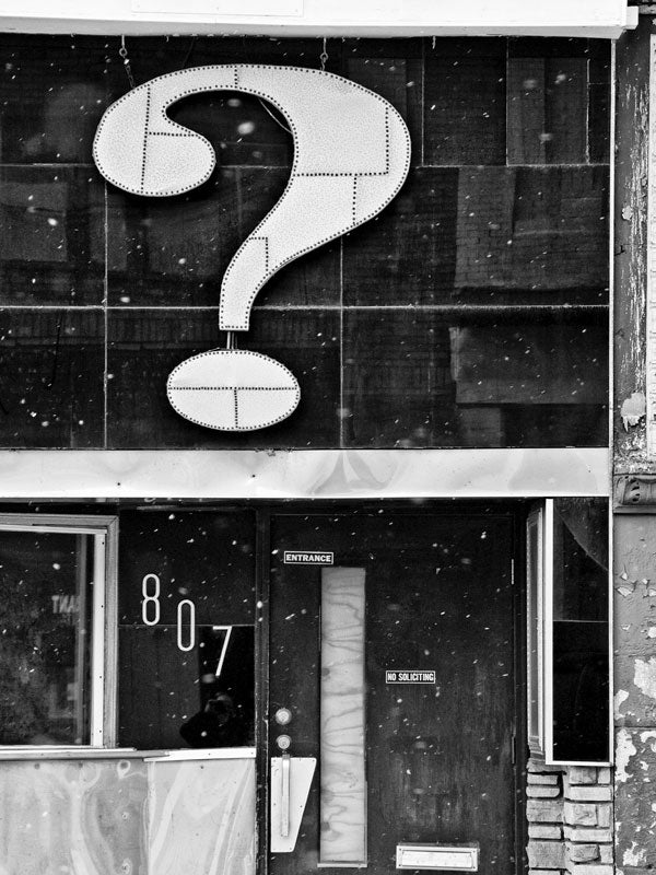 Black and white architectural photograph of a storefront in Milwaukee with a huge question mark above the door, and snow flurries blowing in the air.