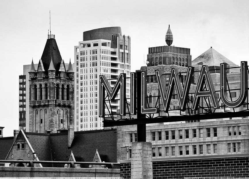 "Black and white photograph of the Milwaukee skyline with the ""Milwaukee"" sign from the Milwaukee Public Market in the foreground."