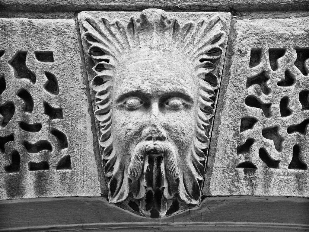 Black and white photograph of the carved stone face of Aeolus the God of the Winds on the old Bank of Milwaukee Building