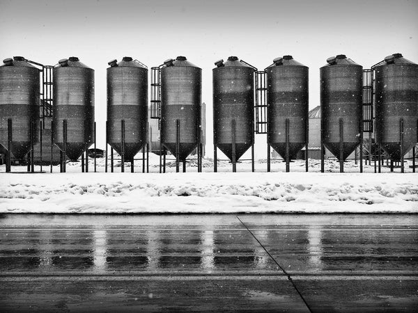 Black and white landscape photograph of a row of dark grain bins reflecting on wet pavement during an active snow storm.