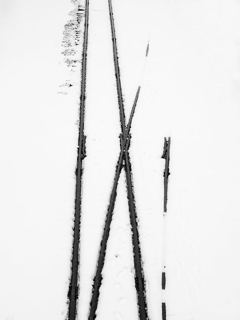 Black and white photograph of railroad tracks seen from above, partially covered in snow.
